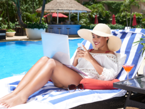 lady on laptop by the pool